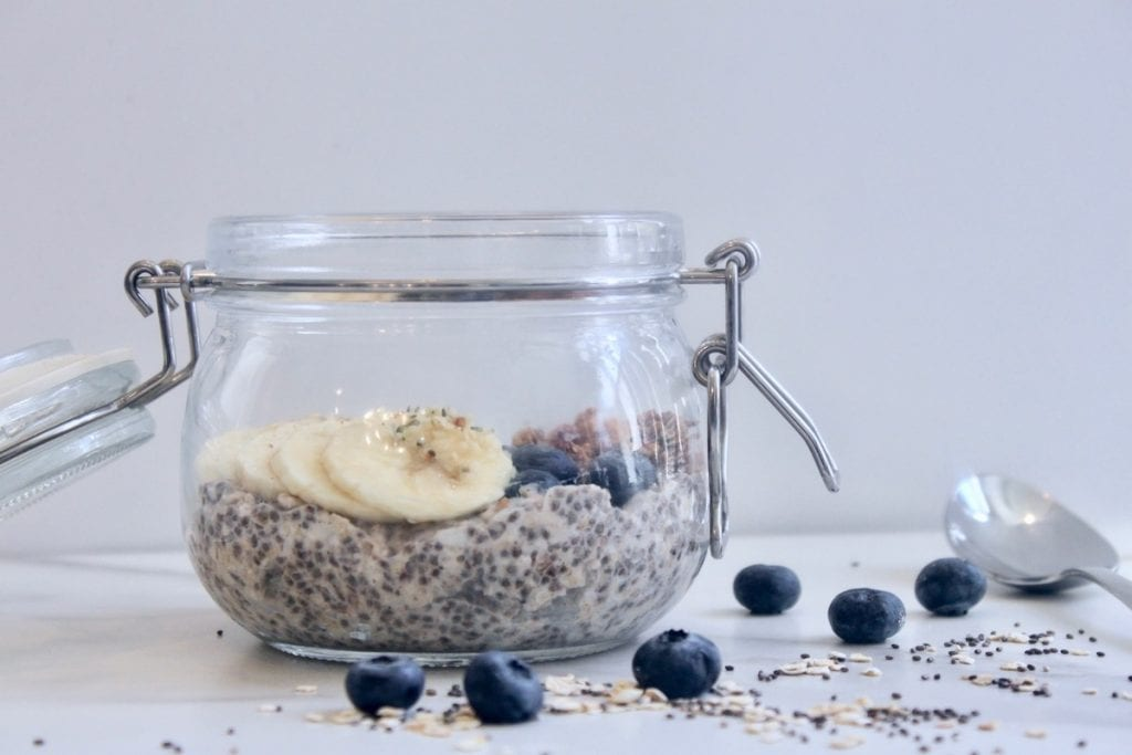 sideview of clear glass jar with lid and silver latch filled with overnight oats and banana and blueberries and oats scattered on white table.