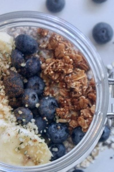 top view of glass bowl of overnight oats topped with sliced bananas, blueberries and granola