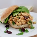 Cherry Chipotle Chicken salad on bun with lettuce on a white place