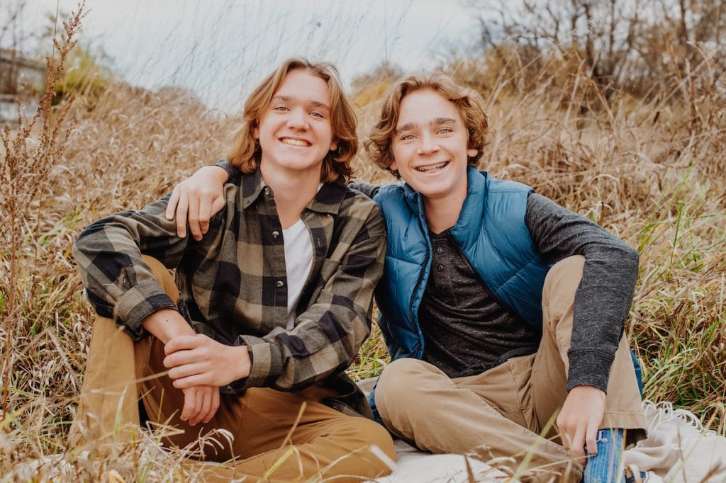 Henry and Charlie, sitting in field, plaid shirt and blue vest, khaki pants