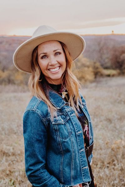 Laura in field with fall colors in a denim jacket, black dress and cream hat