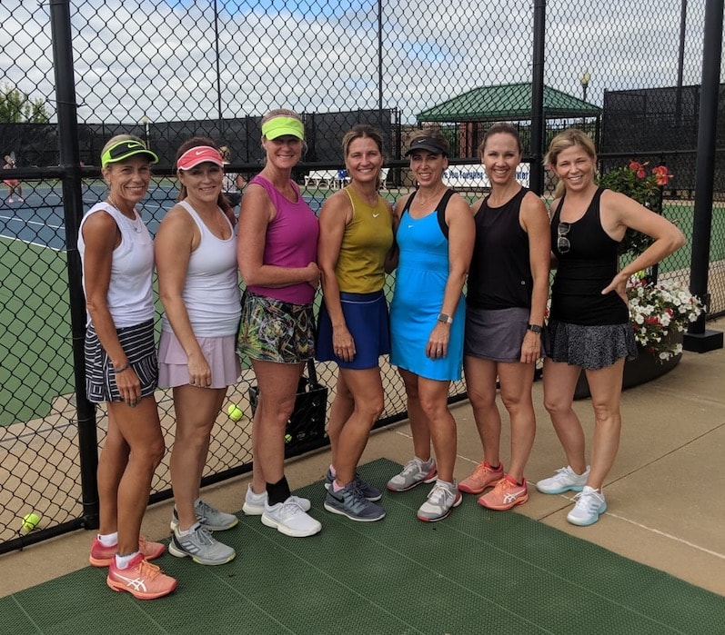7 women in tennis attire after playing a match