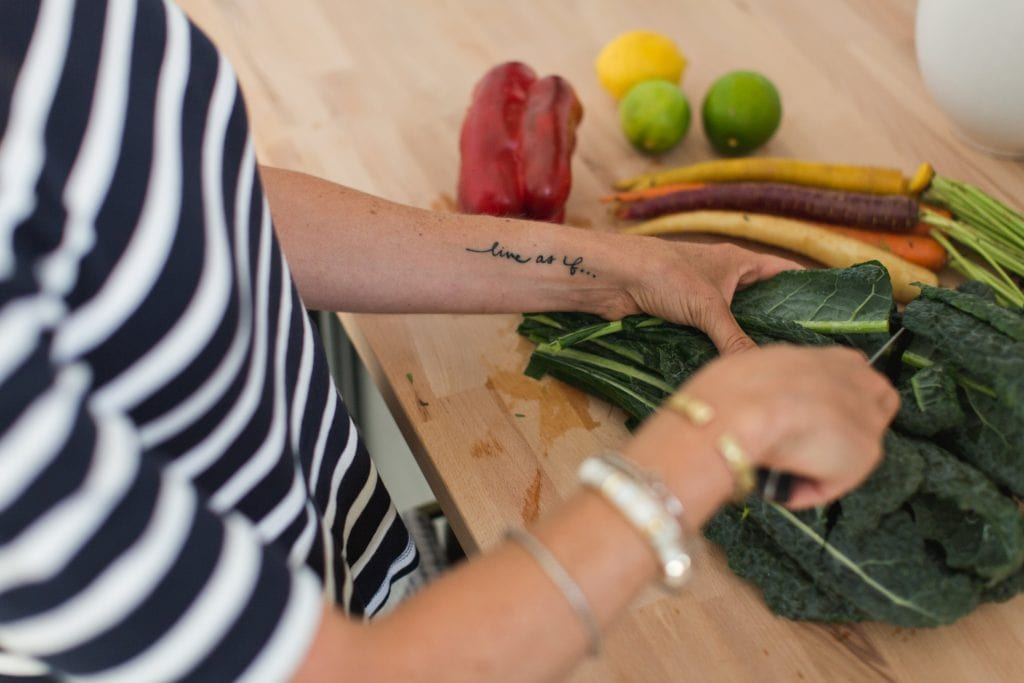 woman's hands cutting a bunch of kale and other vegetables on wood cutting board