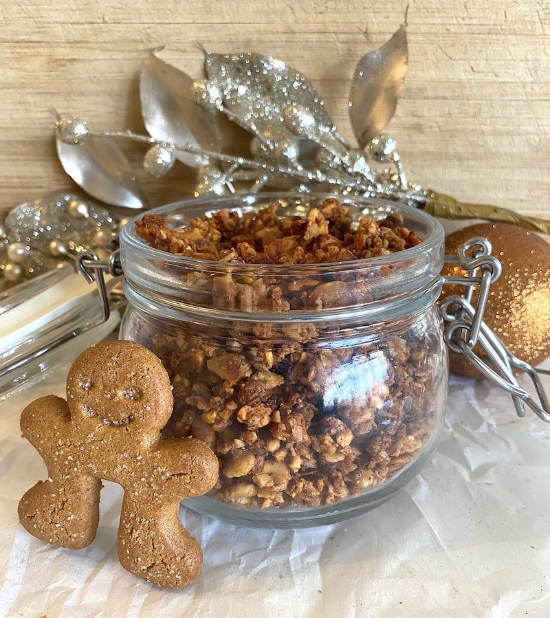 granola in glass jar with gingerbread man leaning against it