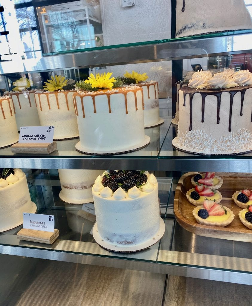 bakery case with several cakes iced in white icing and various toppings