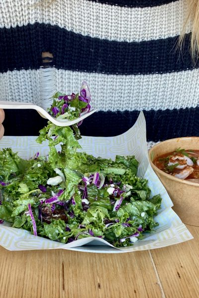 a woman holding a forkful of salad from Unforked wearing a black and white striped sweater