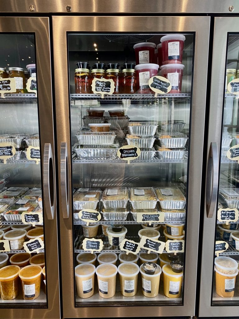 Upright cooler with glass doors filled with prepared food at Caffetteria