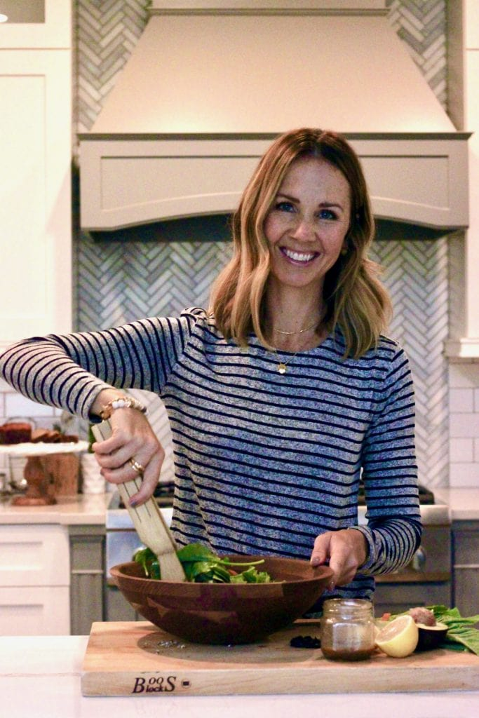 woman in blue and gray striped shirt making a salad in wood bowl