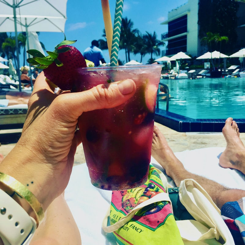 a woman's hand holding a fruity drink at the pool on vacation