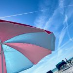 pink and blue beach umbrella against blue sky