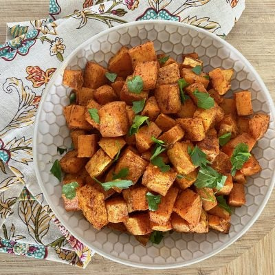 roasted sweet potatoes in a cream bowl with a colorful napkin to the side