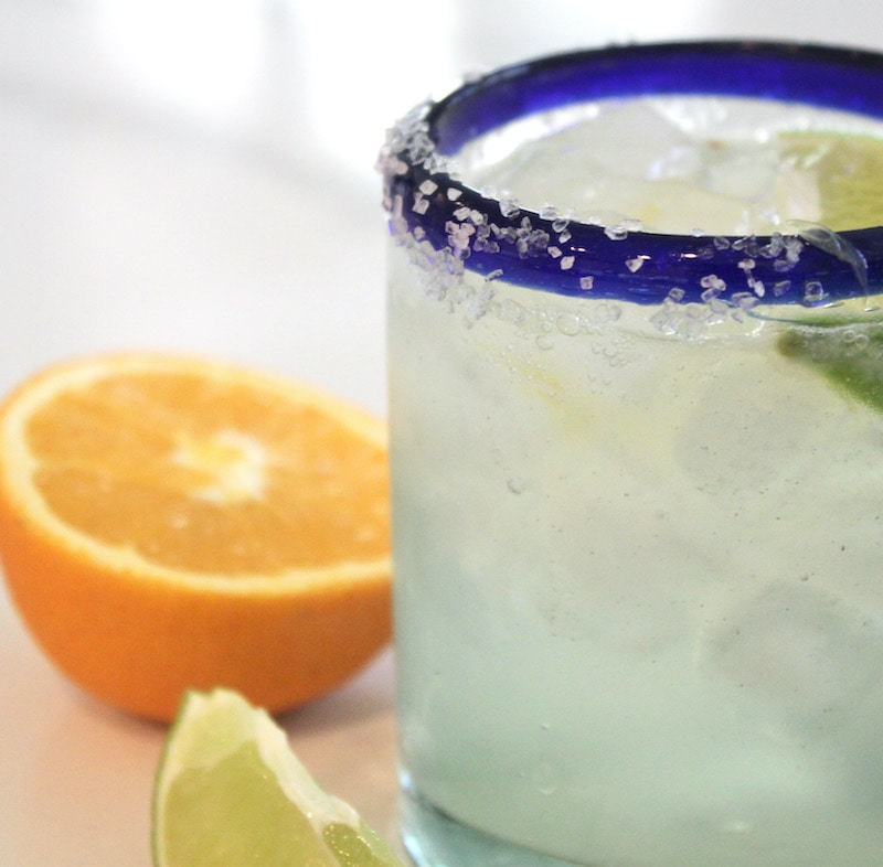 side view of margarita with half an orange on white counter