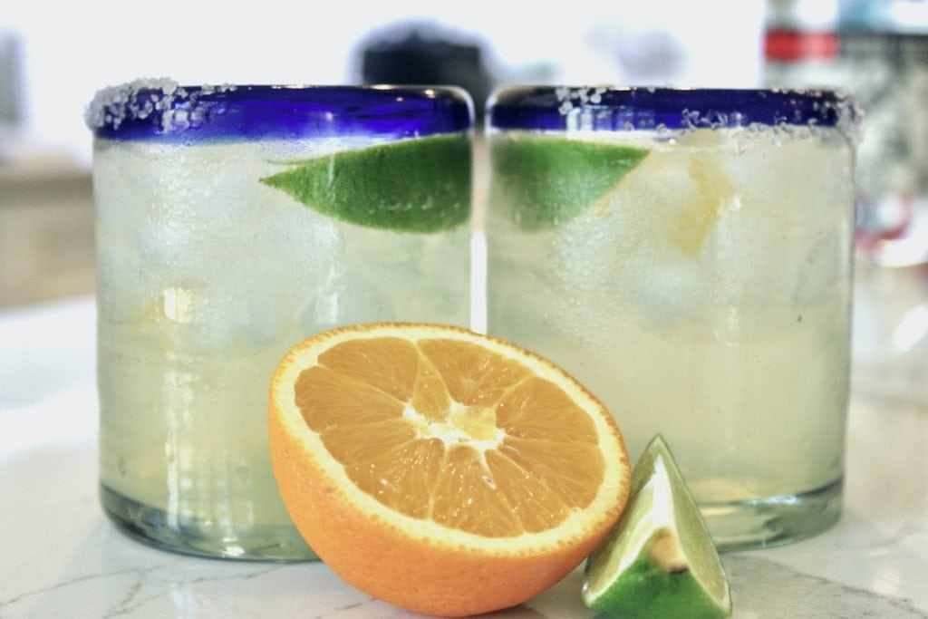 two skinny margaritas in blue rimmed glass with half an orange in front